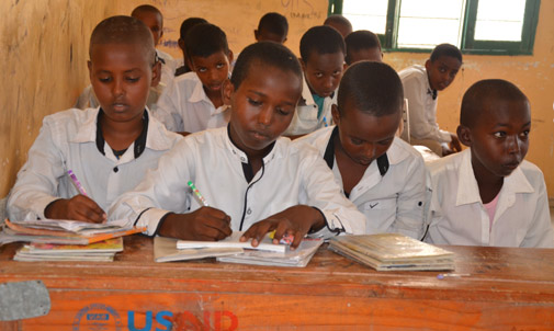 © UNICEF Somalia/2017/Sarman Mohamed, second from the left, flanked by his schoolmates in their classroom at Omar bin Khataab primary school in Berbera, which is supported by the Joint Programme on Local Governance and Decentralised Service Delivery (JPLG).