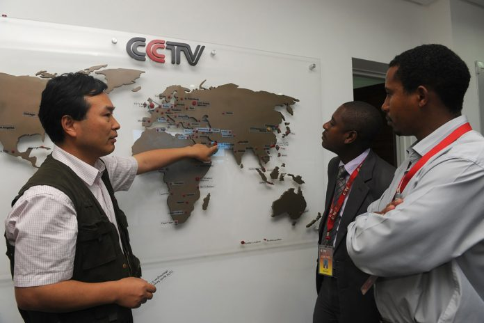 The managing editor of China Central Television Africa, Pang Xinhua, shows a local journalist in Nairobi how the organization has expanded in different parts of Africa on June 12, 2012. (Simon Maina/AFP/GettyImages)