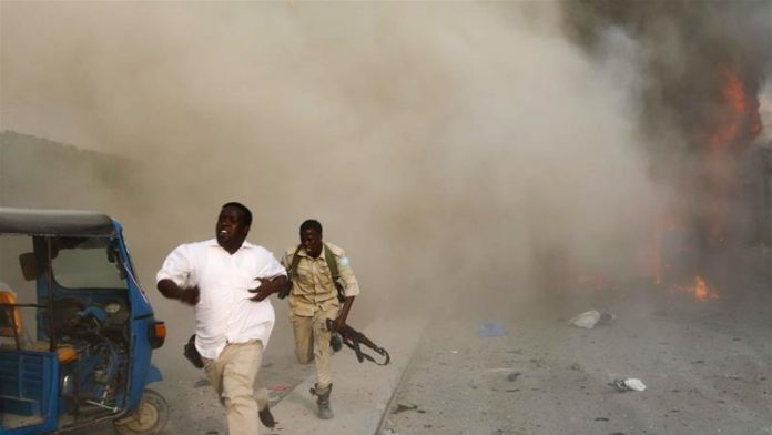 Security officers run from the scene of the blast [Feisal Omar/Reuters]
