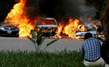 (Thomas Mukoya/Reuters) Cars are seen on fire at the scene of explosions and gunshots in Nairobi, Kenya, Jan. 15, 2019.