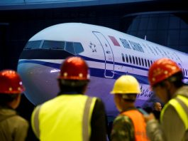 Workers attend a ceremony marking the 1st delivery of a Boeing 737 Max 8 airplane to Air China at the Boeing Zhoushan completion center in Zhoushan, Zhejiang province, China, December 15, 2018. REUTERS/Thomas Peter/Files