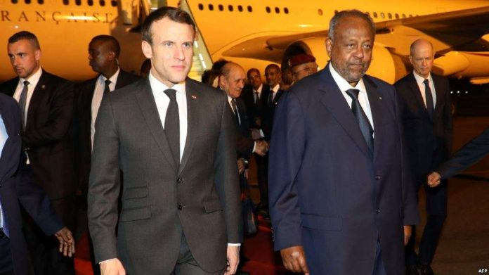 French president Emmanuel Macron (C) is welcomed by Djibouti's president Ismail Omar Guelleh upon his arrival at Djibouti's airport, March 11, 2019, in Djibouti, at the start of his trip to eastern Africa