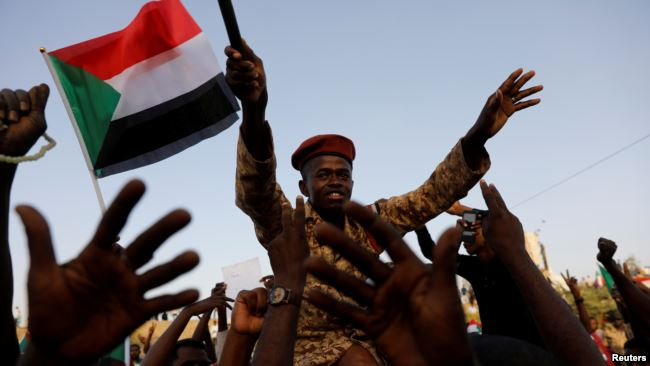 A Sudanese soldier sits on the shoulders of a demonstrator, cheering with the crowd outside Defense Ministry in Khartoum, Sudan, April 16, 2019.