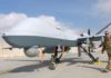 FILE - U.S. Air Force officer passes in front of a MQ-9 Reaper drone, one of a squadron that has arrived to step up the fight against the Taliban, at the Kandahar air base, Afghanistan, Jan. 23, 2018.