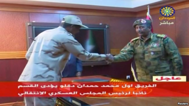 Sudan's General Mohamed Hamdan Dagalo, known as Hemedti, head of the Rapid Support Forces, is sworn-in as the appointed deputy of Sudan's Transitional Military Council, standing before the head of transitional council, Lieutenant General Abdel Fattah al-Burhan