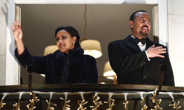 Abiy Ahmed and his wife Zinash Tayachew wave from the balcony of the Grand Hotel in Oslo on 10 December during a torch parade in honour of his Nobel peace prize. Photograph: Terje Pedersen/NTB Scanpix/AFP via Getty Images