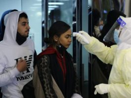 Passengers coming from China wearing masks are checked by Saudi Health Ministry employees upon their arrival at King Khalid International Airport, in Riyadh, Saudi Arabia. (Reuters
