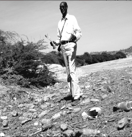 """Ahmed writes, """"On one of my most exciting and longest walks through our beautiful land, I found a plastic water bottle containing a young germinated plant in Waahen watercourse, but unfortunately doomed to certain death. Thousands of tons of plastic generated by Hargeysa citizens end up in the sea."""" Photograph of Ahmed, amidst plastic waste, was taken in 2013 by Jama Hussein."""