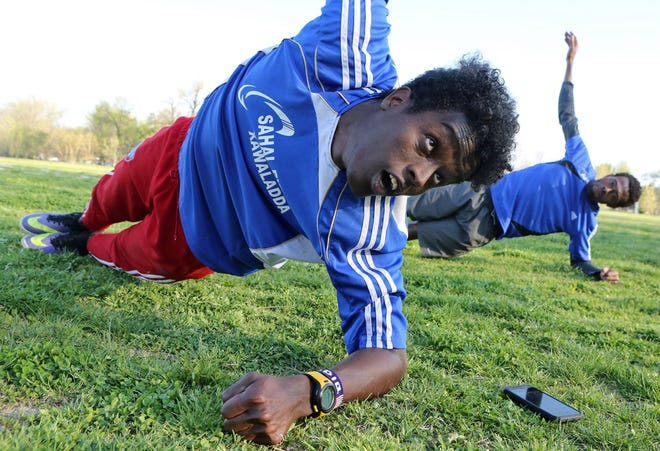 Saadiq Mohammed and Sa'ad Hussein stretch in Forest Park on April 7, 2016, in St. Louis, as they prepare to practice soccer. J.B. Forbes/St. Louis Post-Dispatch (TNS)