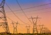a Series of electrical transmission tower with power lines criss crossing at sunset.