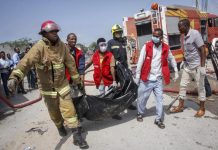 Medical workers carry the body of a civilian who was killed in a suicide car bomb attack that targeted the city's police commissioner in Mogadishu, Somalia Saturday, July 10, 2021. At least nine people are dead and others wounded after the large explosion, a health official at the Medina hospital said, noting that the toll reflected only the dead and wounded brought there. (AP Photo/Farah Abdi Warsameh)