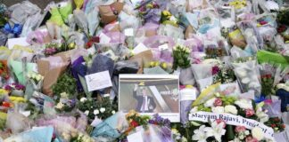 A photograph of member of Parliament David Amess is seen among the flower tribute near the Belfairs Methodist Church in Eastwood Road North, where Amess died after he was stabbed several times on Friday, in Leigh-on-Sea, Essex, England, Sunday, Oct. 17, 2021. The slaying Friday of the 69-year-old Conservative lawmaker Amess during his regular weekly meeting with local voters has caused shock and anxiety across Britain's political spectrum, just five years after Labour Party lawmaker Jo Cox was murdered by a far-right extremist in her small-town constituency. (Kirsty O'Connor/PA via AP)