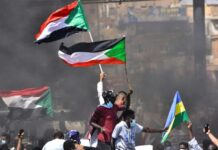 In this file picture taken on October 21, 2021, Sudanese demonstrators raise national flags as they take part in a protest in the city of Khartoum Bahri to demand the government's transition to civilian rule (AFP/-)
